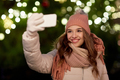 young woman taking selfie over christmas tree