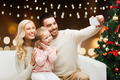 family taking selfie with smartphone at christmas