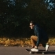 Man on a Skateboard on an Autumn Road - VideoHive Item for Sale
