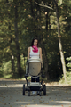 Attractive stylish woman pushing a baby stroller - PhotoDune Item for Sale