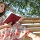 Girl with a Book on a Bench in the Park - VideoHive Item for Sale