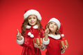 Two happy girls in santa claus hats with gift boxes