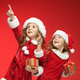 Two happy girls in santa claus hats with gift boxes - PhotoDune Item for Sale