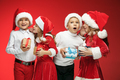 Two happy girls and boys in santa claus hats with gift boxes