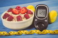 Glucometer, fresh oatmeal with fruits, centimeter and dumbbells