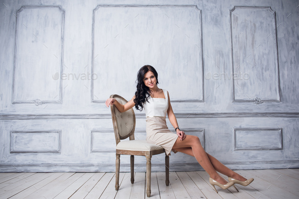 Fashion shot of young beautiful woman in white short dress sitting in antique chair - Stock Photo - Images