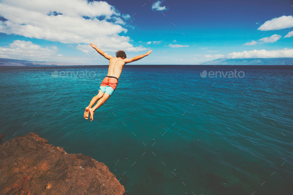 Friends cliff jumping into the ocean - Stock Photo - Images