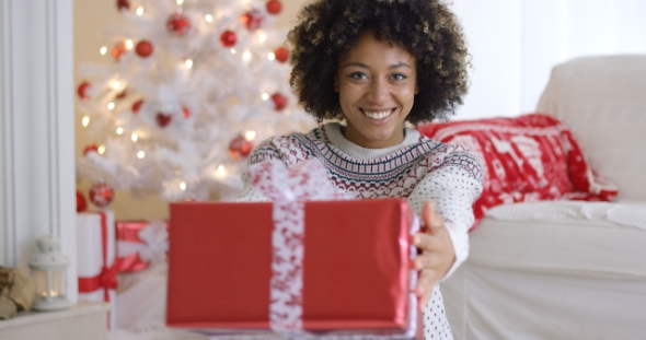 Smiling Friendly Woman Offering a Christmas Gift
