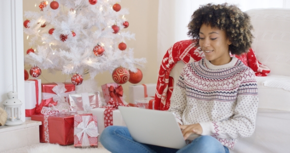 Young Woman Typing on a Laptop at Christmas