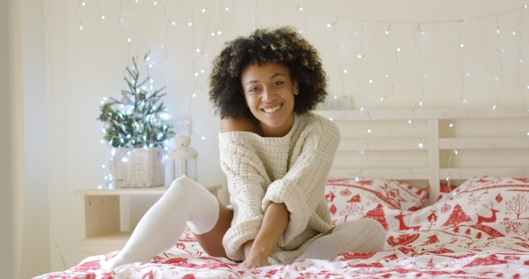 Cute Young Woman Relaxing at Home at Christmas