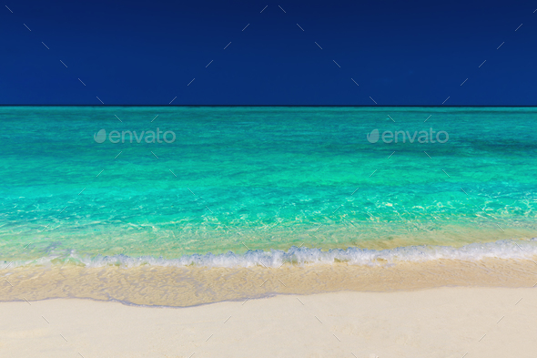 Vibrant green tropical sea, sand and blue sky - Stock Photo - Images