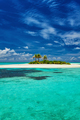 Small island surrounder by reef and beach in Maldives