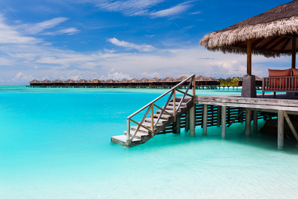 Over water bungalow with steps into blue lagoon - Stock Photo - Images