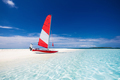 Sailing boat with red sail on a beach of deserted tropical islan