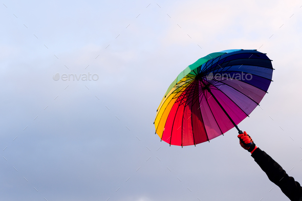 Umbrella in hand against sky background - Stock Photo - Images