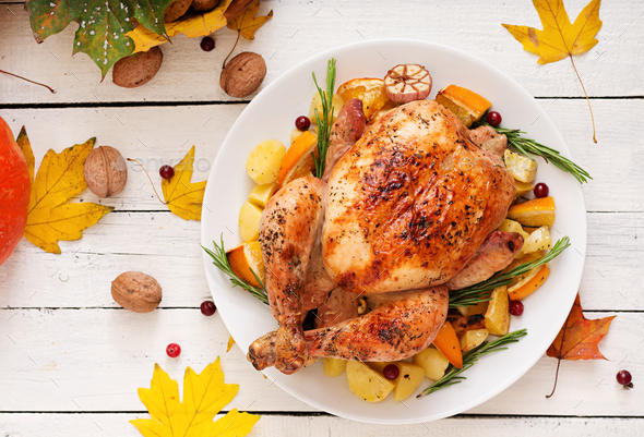 Roasted turkey garnished with cranberries on a rustic style table - Stock Photo - Images