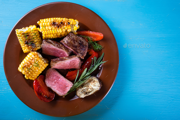 Slices of fried meat with corn and vegetables on plate - Stock Photo - Images
