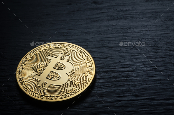 Golden shiny bitcoin on a black wooden background - Stock Photo - Images
