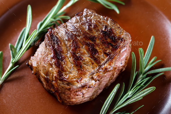 Piece of juicy roast meat with rosemary on a clay plate - Stock Photo - Images