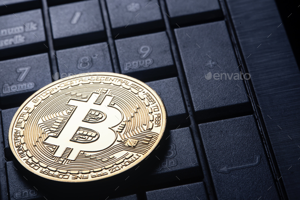 Virtual currency is the golden bitcoin on the computer keyboard - Stock Photo - Images
