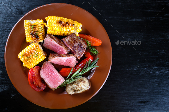 Slices of mildly fried steak with corn and vegetables - Stock Photo - Images