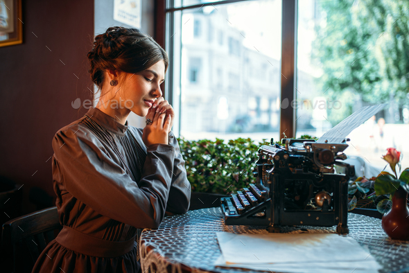 Smiling lady sits by table with ancient typewriter - Stock Photo - Images