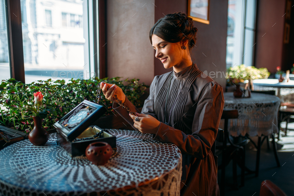Young happy woman in cafe with casket and jewelry - Stock Photo - Images