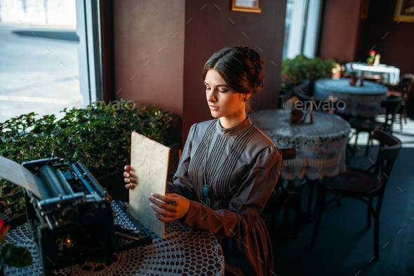 Happy young woman sits by the table in cafe - Stock Photo - Images