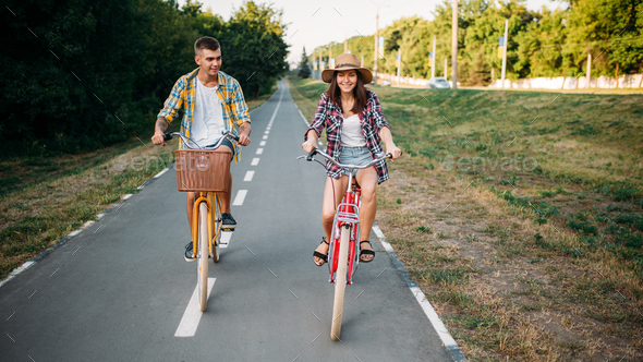Love couple riding on retro bikes in summer park - Stock Photo - Images