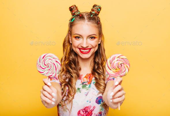 Smiling lady holding two huge colorful lollypops - Stock Photo - Images