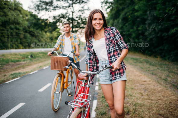 Young man and woman walking on retro bikes - Stock Photo - Images