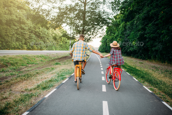 Love couple riding on vintage bikes - Stock Photo - Images