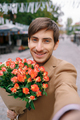 Smiling man making selfie with flowers