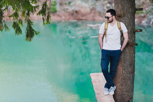 Bearded man model poses alongside a Green water Lake. - Stock Photo - Images