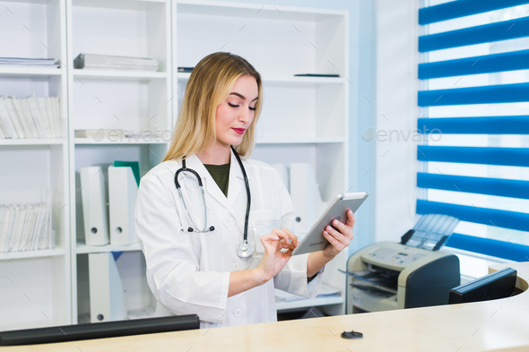 Young female receptionist holding tablet computer in hospital - Stock Photo - Images