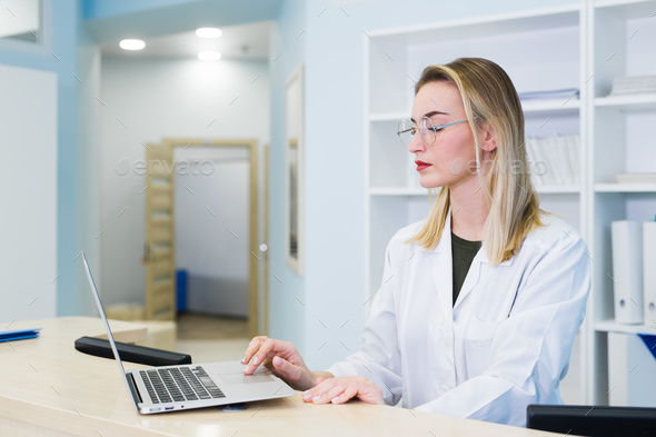 Smiling nurse with laptop scheduling appointment for male patient at reception - Stock Photo - Images