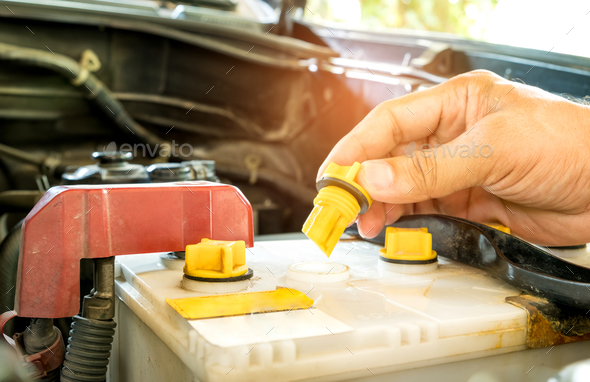 Daily car check,Check out the distilled car battery. - Stock Photo - Images