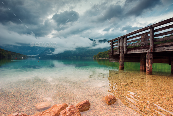 Wooden pier at Bohinj lake on cloudy autumn day - Stock Photo - Images