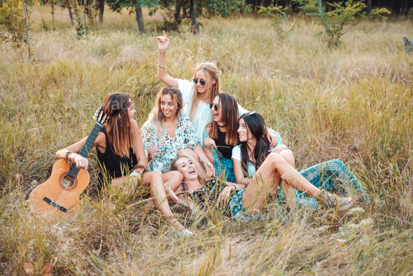 Six girls in nature are sitting on the grass. - Stock Photo - Images