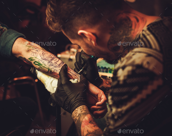 Tattoo artist makes a tattoo on a man's hand. - Stock Photo - Images