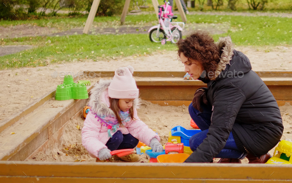 Mother playing with her daughter in a sandbox - Stock Photo - Images
