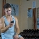 Athletic Man Sitting in Fitness Gym After Workout, Chatting Online Smart Phone - VideoHive Item for Sale