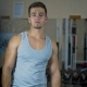 In the Gym, a Man Looks in the Mirror and Makes Swings with Muscular Arms - VideoHive Item for Sale
