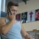 Young Man with Smartphone in Gym Call Friends