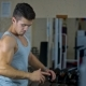 Man Looks in the Mirror in the Gym and Makes Swings with Muscular Arms