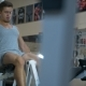 Young Athlitic Man Does Leg Extensions in Gym