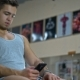 Athletic Man Sitting in Fitness Gym After Workout, Chatting Online Smart Phone