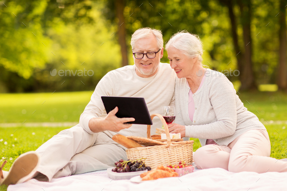 happy senior couple having picnic at summer park - Stock Photo - Images