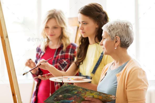 women with easel and palettes at art school - Stock Photo - Images