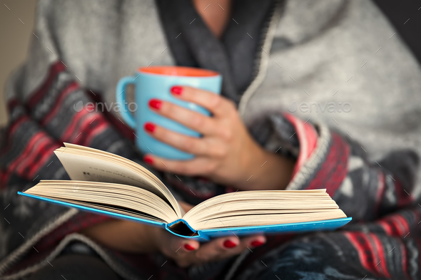 Reading a book on a long winter evening - Stock Photo - Images